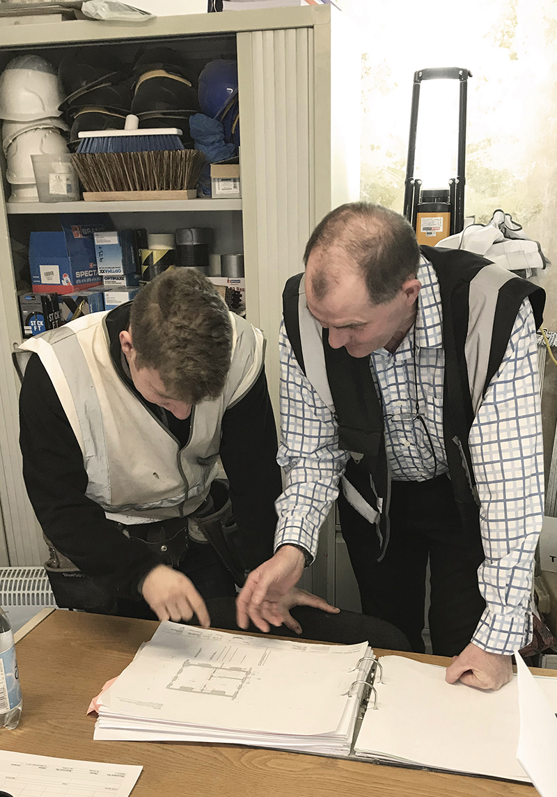 Apprentice and site manager look over drawings