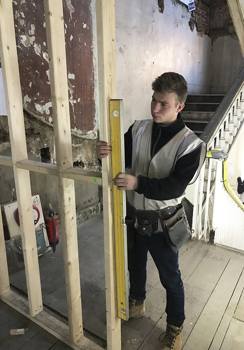 Construction apprentice checking his work