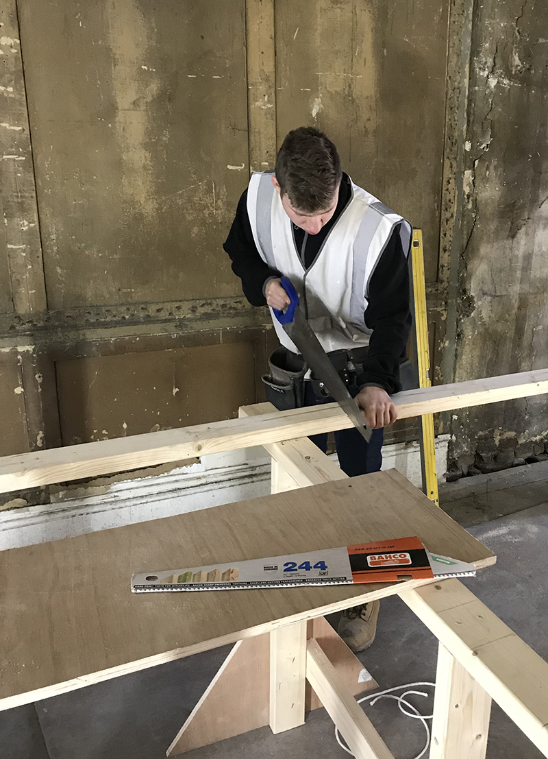 Carpentry apprentice sawing